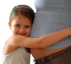 малыш обнимает беременную маму